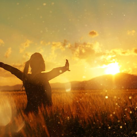 silhouette in the sunset, young woman with her arms raised enjoying summer twilight in the middle of nature.
